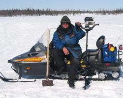 Рыбак с ледобуром на снегоходе