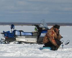 Снегоход и рыбак удит рыбу