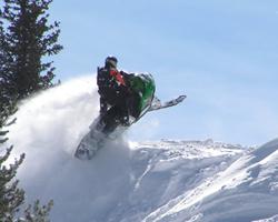 Прыжок на снегоходе на склоне