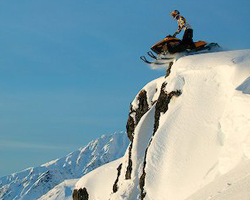 Горный снегоход на обрыве перед прыжком