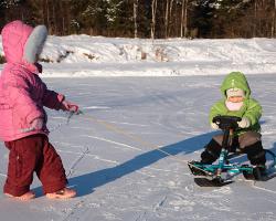 Ребенок тянет другого на снегокате