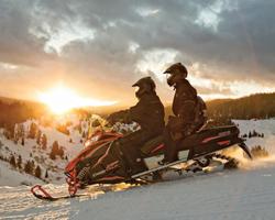 Люди на снегоходе на фоне заката