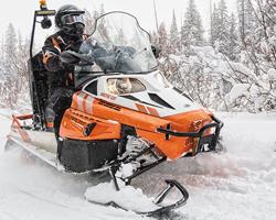 Оранжевый снегоход в снежном лесу