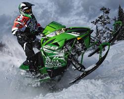 Человек едет на зеленом снегоходе