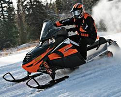 Человек едет на оранжевом снегоходе