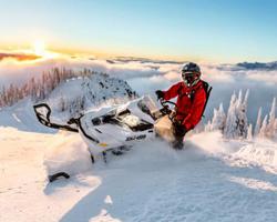 Снегоход на вершине горы, восходит солнце