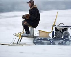 Мужчина едет зимой на мотобуксировщике с лыжным моудлем