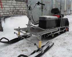 Мотобуксировщик с лыжным модулем около гаража