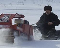 Мотобуксировщик тянет сани с человеком по глубокому снегу