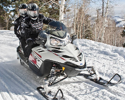 Мужчины на снегоходе Polaris едут по снегу