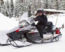 Мужчина на снегоходе Polaris едет по снегу