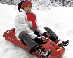 Мальчик едет на санях с рулем