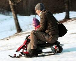Мужчина с ребенком едет на снегокате