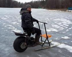 Мужчина едет на мотосанях по льду