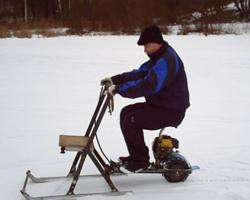 Мужчина едет на мотосанях сидя