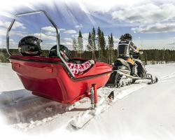 Пассажиры едут в снегоходных санях