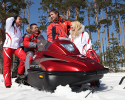 Два мужчины и две женщины на красном снегоходе
