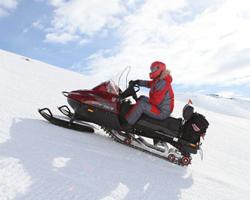 Мужчина едет в гору на снегоходе