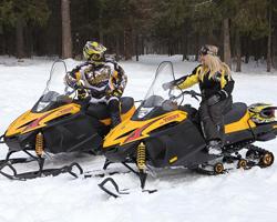Двое на черно-желтых снегоходах в лесу