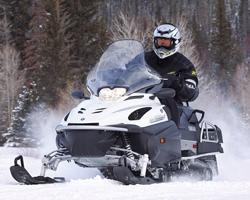 Человек едет на черно-белом снегоходе