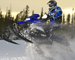 Человек прыгает на синем снегоходе
