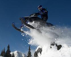Человек прыгает на снегоходе на фоне неба