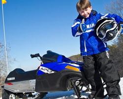 Мальчик в синем рядом со снегоходом
