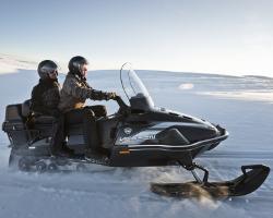 Двое едут на снегоходе