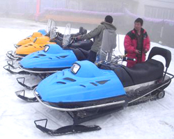 Два китайца около трех снегоходов