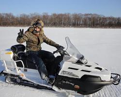 Человек едет по полю на белом снегоходе