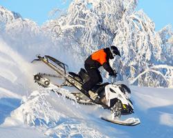 Человек едет со склона на снегоходе