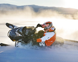 Человек едет в наклон на снегоходе