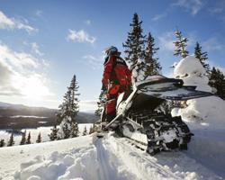Человек на снегоходе, на горизонте - солнце и горы
