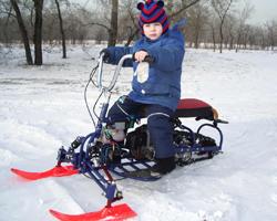 Ребенок в вязаной шапочке на самодельном снегоходе