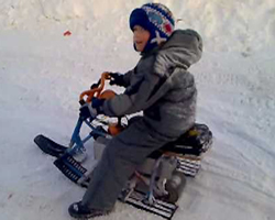 Ребенок на самодельном снегоходе на базе снегоката