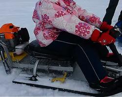 Девочка в розовой куртке на детском самодельном снегоходе