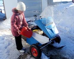 Девочка заливает бензин в снегоход