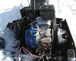 Синий двигатель, установленный на черный снегоход