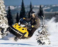 Мужчина на черно-желтом снегоходе между снежных ёлок