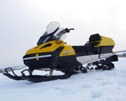 Черно-желтый снегоход в снежном поле