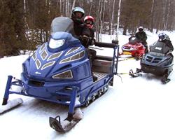 Утилитарный снегоход тащит на буксире еще два снегохода
